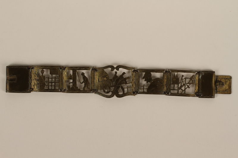 2007.45.3 front Brass bracelet with cutout designs of scenes of daily life made in Łódź Ghetto