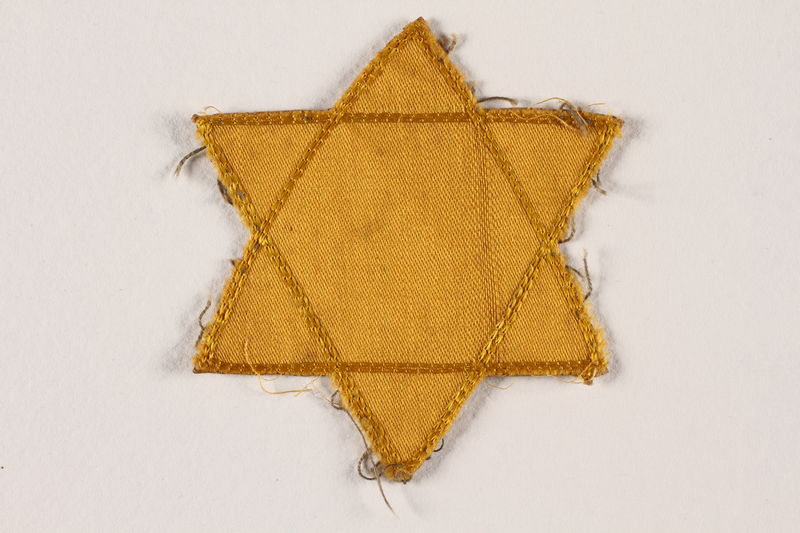 2007.45.5 front Yellow cloth Star of David badge with a blank center