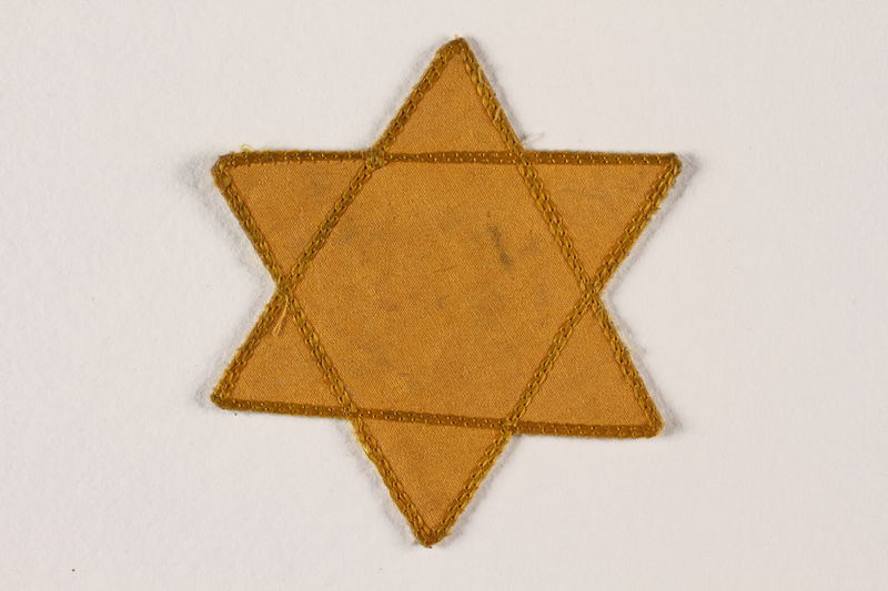 2007.45.6 front Yellow cloth Star of David badge with a blank center