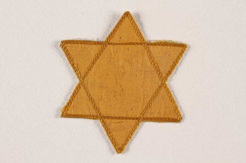 2007.45.8 front Yellow cloth Star of David badge with a blank center