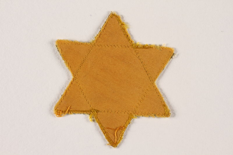2007.45.10 front Yellow cloth Star of David badge with a blank center