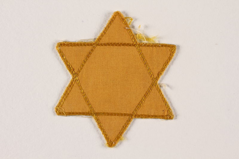 2007.45.11 front Yellow cloth Star of David badge with a blank center