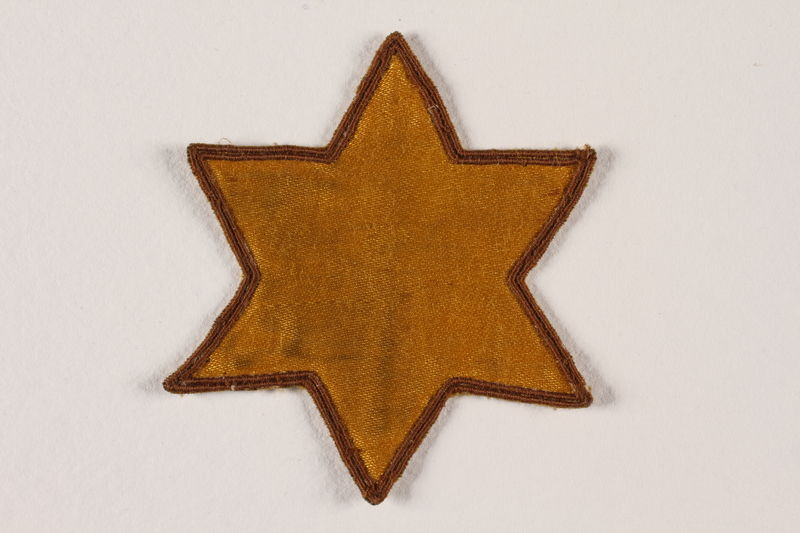2007.45.12 front Yellow cloth Star of David badge with a blank center