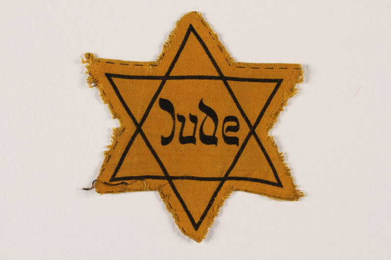 2007.45.14 front Yellow cloth Star of David badge with Jude printed in the center