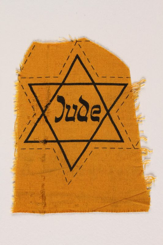 2007.45.15 front Unused yellow cloth Star of David badge with Jude printed in the center
