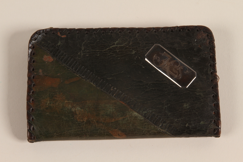 2007.101.7 front Monogrammed black and tan laced leather wallet used by a German Jewish refugee