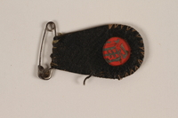 2007.101.9 front Red enamel permit tag in leather holder issued to a German Jewish refugee  Click to enlarge