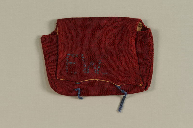 2007.151.2 front Red monogrammed knit purse made by an inmate in a forced labor camp