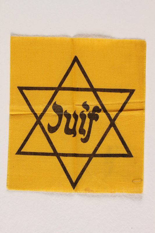 2001.233.2 front Yellow cloth Star of David badge with Juif printed in center