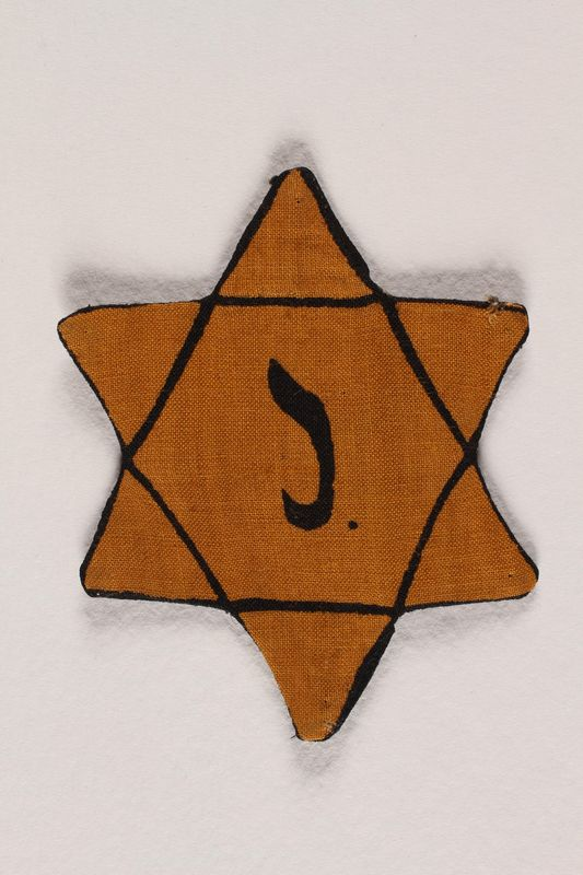 2001.326.5 front Yellow cloth Star of David badge with the letter J. to identify a Belgian Jew