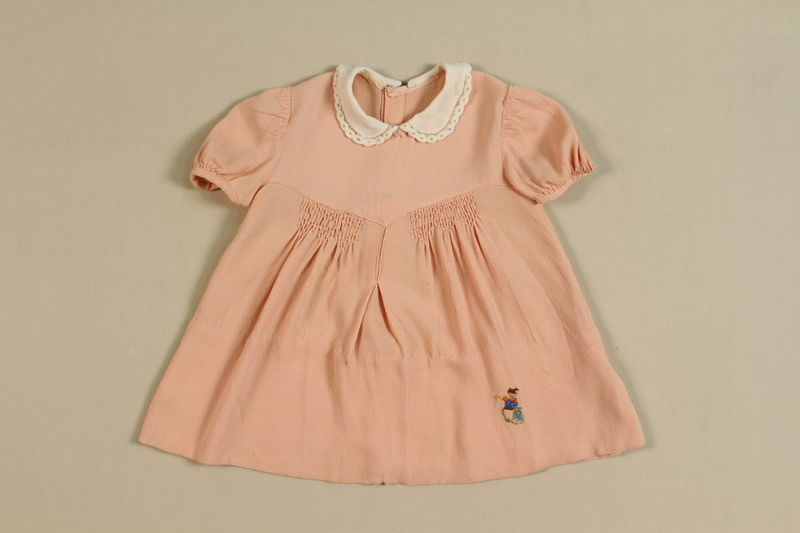 2002.438.8 front Pink embroidered dress once worn by a young girl killed in a bombing raid