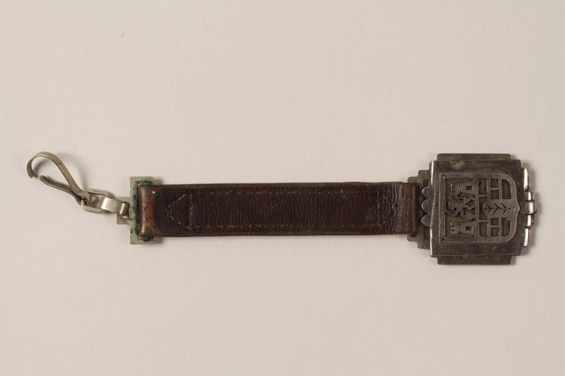 1989.192.1 front Decorative metal piece attached to a short leather strap with a clip