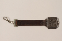 1989.192.1 front Decorative metal piece attached to a short leather strap with a clip  Click to enlarge