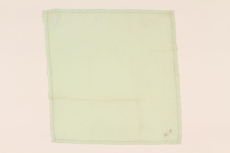 2003.454.7 front Light green handkerchief with a pink monogram carried by a Kindertransport refugee