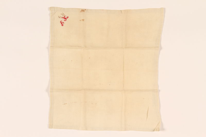 2003.454.12 front Offwhite handkerchief with a red monogram carried by a Kindertransport refugee