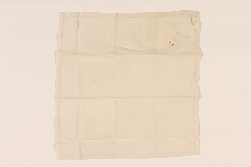 2003.454.14 front Offwhite handkerchief with floral whitework and a yellow monogram carried by a Kindertransport refugee