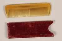 2003.454.23_a-b front Yellow plastic comb with cardboard case carried by a Kindertransport refugee  Click to enlarge