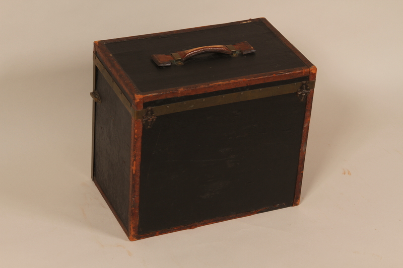2004.322.2 back Small square black painted wooden trunk used by Jewish refugees