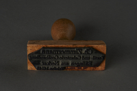 2004.593.3 bottom Rubber stamp from a Jewish refugee's postwar business  Click to enlarge