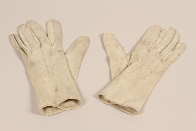 2004.628.3_a-b front Pair of men's white leather driving gloves carried by a Jewish refugee during his escape from Vienna
