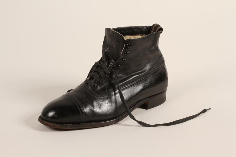 2004.628.5_a front Pair of men's black leather lace-up ankle boots owned by a Jewish refugee during his escape from Vienna