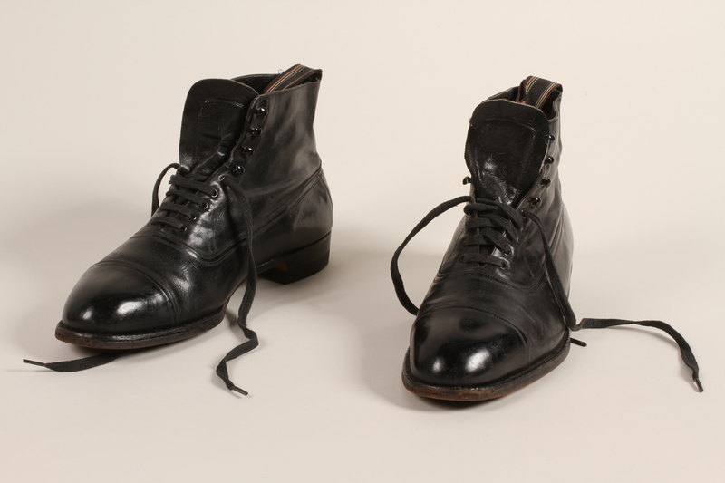2004.628.5_a-b front Pair of men's black leather lace-up ankle boots owned by a Jewish refugee during his escape from Vienna