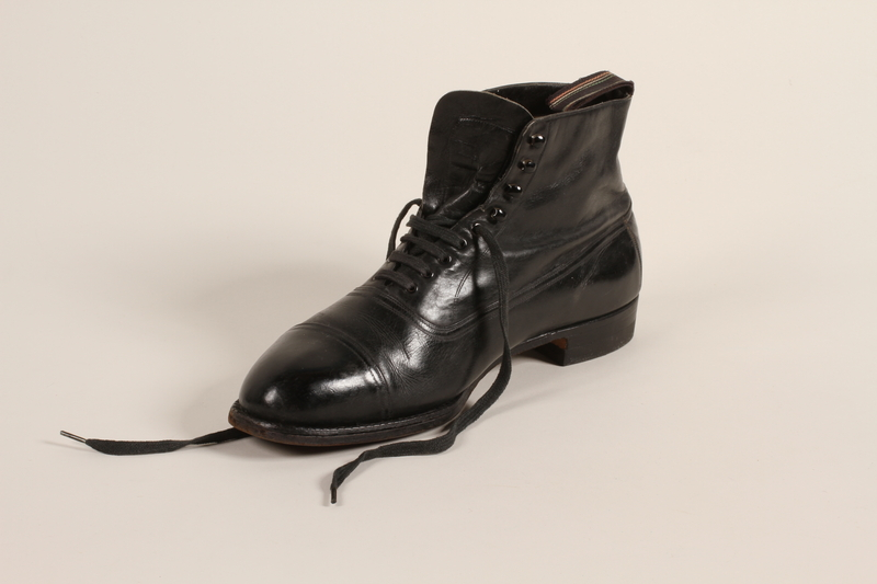 2004.628.5_b front Pair of men's black leather lace-up ankle boots owned by a Jewish refugee during his escape from Vienna