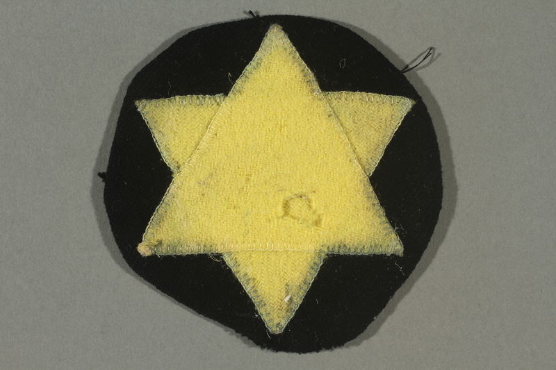2016.487.1 front Circular patch with a yellow Star of David worn by a Jewish Romanian woman