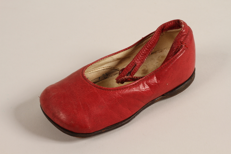 1996.165.2 a front Pair of red leather toddler's shoes worn by a child in Łódź Ghetto