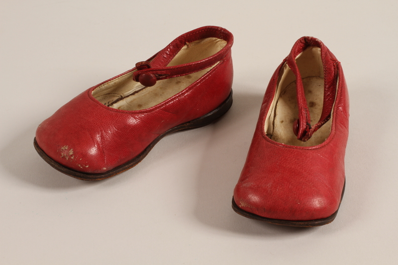 1996.165.2 a-b front Pair of red leather toddler's shoes worn by a child in Łódź Ghetto