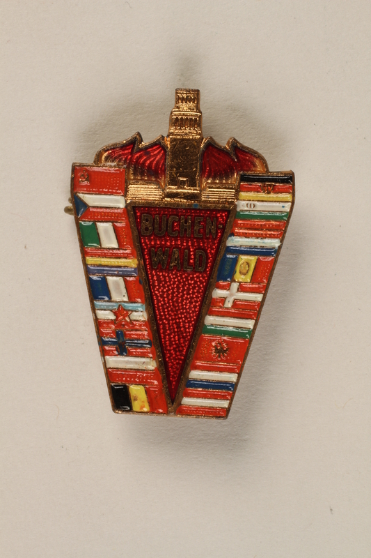 2005.567.5 front Pin issued to a camp survivor with Buchenwald memorial Bell Tower and flags