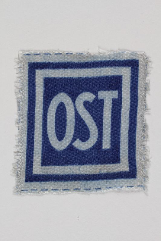 2005.506.4 front Unused forced labor badge, blue field with OST in white letters, to identify a forced laborer from the Soviet Union