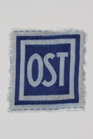 2005.506.4 front Unused forced labor badge, blue field with OST in white letters, to identify a forced laborer from the Soviet Union  Click to enlarge