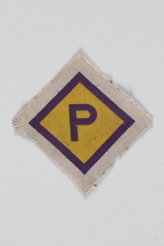 2005.506.5 front Unused forced labor badge, yellow with a purple P, to identify a Polish forced laborer