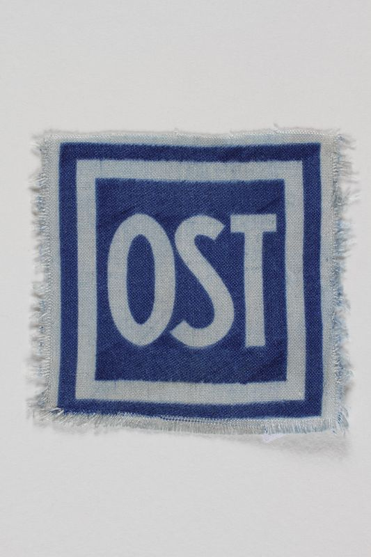 2005.506.7 front Unused forced labor badge, blue field with OST in white letters, to identify a forced laborer from the Soviet Union