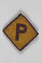 Used forced labor badge, yellow with a purple P, sewn to grey felt backing for use by a Polish forced laborer