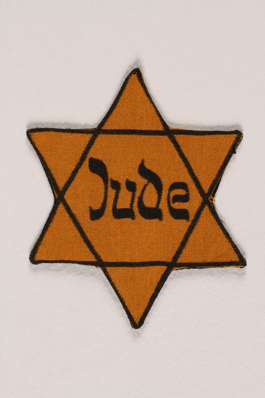 2005.579.5 front Star of David yellow patch with Jude worn by a German Jewish concentration camp inmate