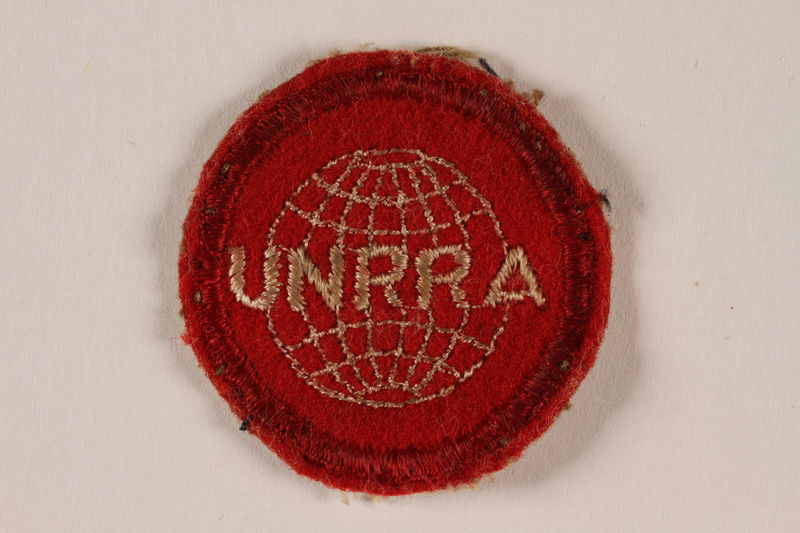 2005.579.6 front UNRRA red felt circular patch with an embroidered globe and acronym worn by a survivor and DP camp relief worker