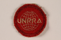 2005.579.6 front UNRRA red felt circular patch with an embroidered globe and acronym worn by a survivor and DP camp relief worker  Click to enlarge