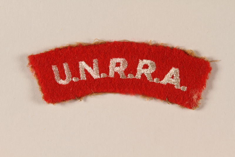 2005.579.8 front UNRRA red felt bar patch worn by a former concentration camp inmate and DP aid worker