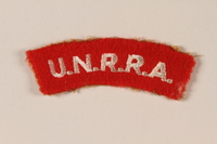 2005.579.8 front UNRRA red felt bar patch worn by a former concentration camp inmate and DP aid worker  Click to enlarge