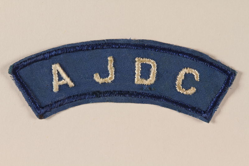 2005.579.12 front American Jewish Joint Distribution Committee blue patch worn by a former concentration camp inmate and refugee aid worker
