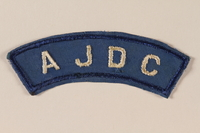 2005.579.12 front American Jewish Joint Distribution Committee blue patch worn by a former concentration camp inmate and refugee aid worker  Click to enlarge