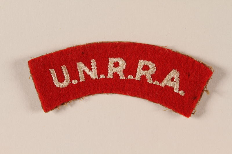 2005.579.11 front UNRRA red felt bar patch embroidered with an acronym worn by a former concentration camp inmate and DP relief worker