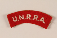 2005.579.11 front UNRRA red felt bar patch embroidered with an acronym worn by a former concentration camp inmate and DP relief worker  Click to enlarge