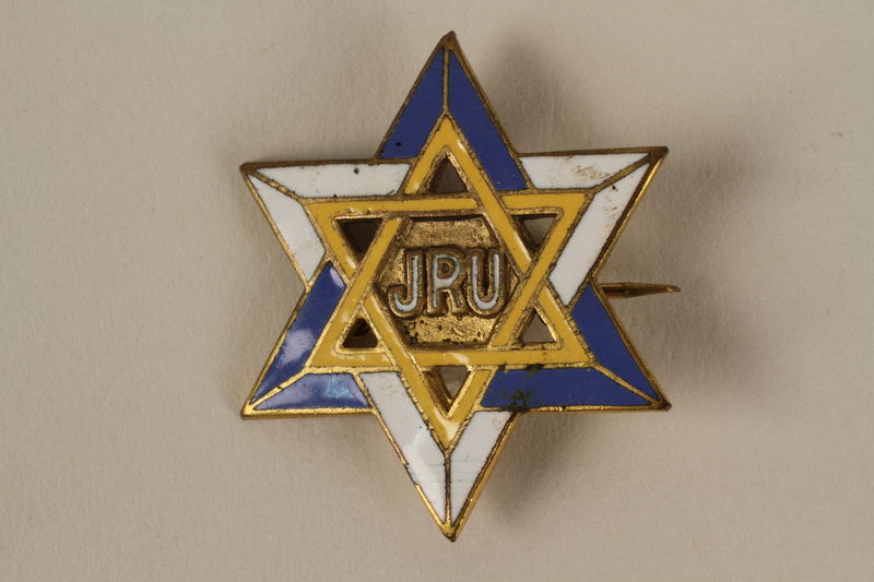 2005.579.15 front Jewish Relief Unit blue, white, and yellow Star of David pin worn by a German Jewish nurse working in the Bergen-Belsen DP camp