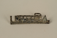 2005.579.16 front Silver metal pin of the acronym UNRRA (United Nations Relief and Rehabilitation Administration) worn by a former concentration camp inmate and refugee aid worker  Click to enlarge