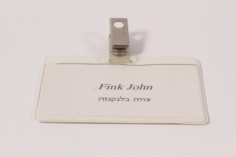 2005.579.7 a-b front Clip on paper name tag and plastic holder worn postwar by a former concentration camp inmate and dp camp relief worker