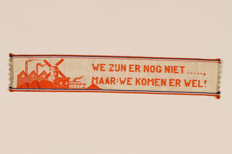 2006.221.2 front Victory ribbon distributed by Canadian troops in the Netherlands given to a young child who had lived in hiding