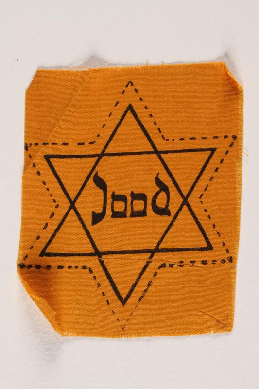 2006.476.2 front Unused yellow Star of David badge printed with Jood